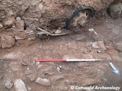 Rough stone wall 102, bonded with brown sandy mortar. Images also shows artefactual material (automotive components, in this case a tyre) typical of mid-20th century activity. Copyright: Cotswold Archaeology